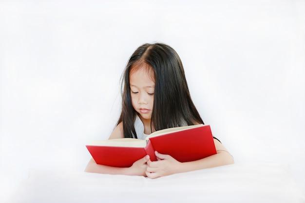 Mooi klein aziatisch de lezings hardcover boek die van het kindmeisje met hoofdkussen op witte achtergrond liggen.