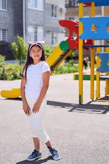 Mooi klein aziatisch meisje met zwart haar in witte kleren op de speelplaats