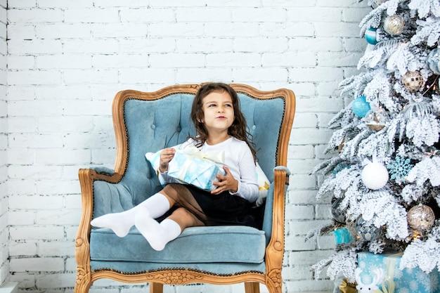 Mooi klein babymeisje thuis voor kerstmis met kerstboom en cadeaus