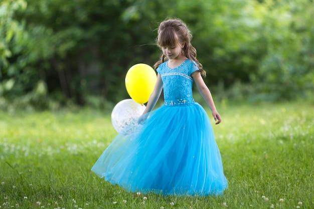 Mooi klein blond langharig meisje in mooie lange blauwe avond dressground.