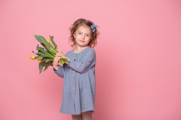 Mooi klein blond meisje in blu jurk met boeket gele tulpen op roze