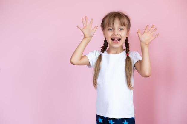 Mooi klein blond meisje met lang haar in het witte t-shirt glimlachen
