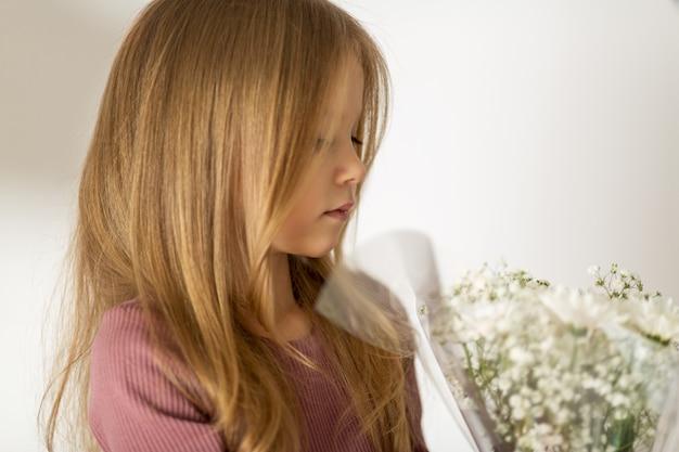 Mooi klein blond meisje met lang haar met een boeket bloemen