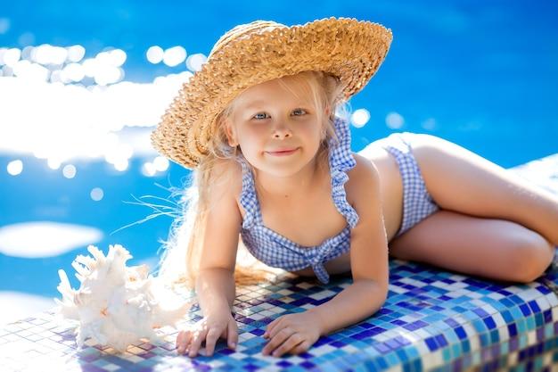 Mooi klein blond meisje met strohoed en een zwempak ligt aan de rand van het zwembad met schelp