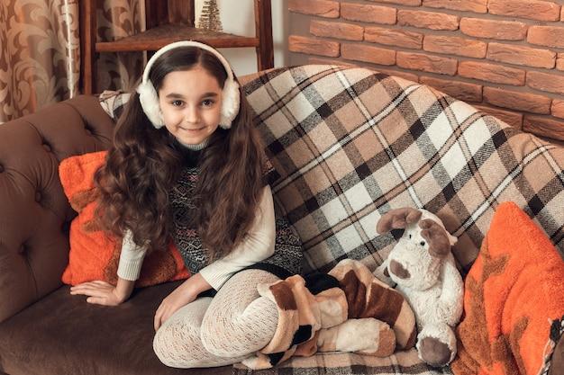 Mooi klein donkerbruin meisje met lange haarzitting op een bank bij kerstmis verfraaide ruimte.