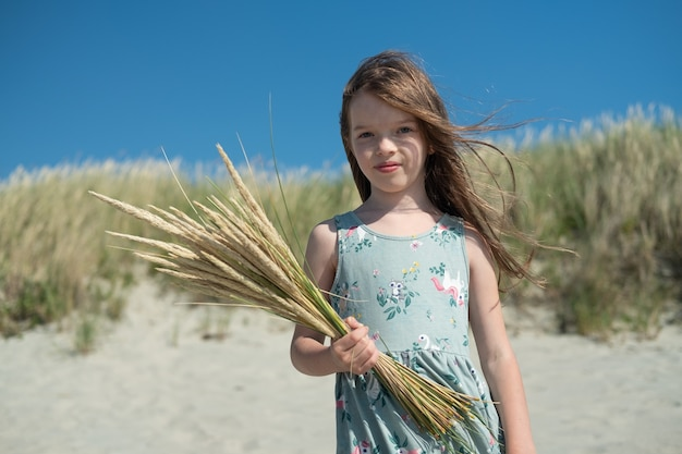 Mooi klein gelukkig meisje op het strand met een boeket van aartjes in haar handen zomertijd