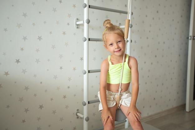 Mooi klein kaukasisch meisje thuis in de buurt van de hangende ladder