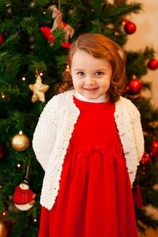 Mooi klein kind in de buurt van de kerstboom.