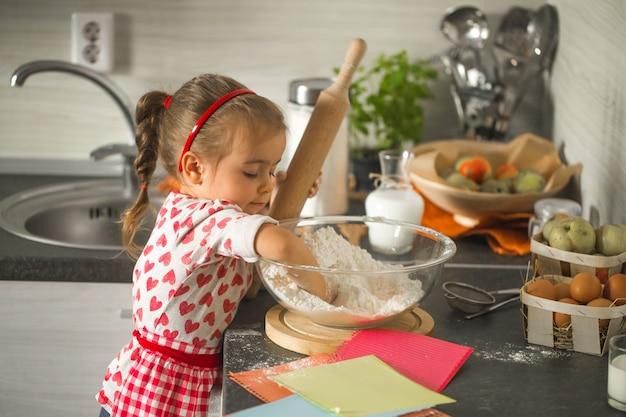 Mooi klein meisje baker op keuken