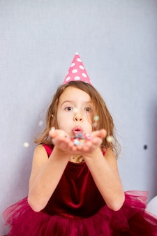 Mooi klein meisje blaast veelkleurige confetti op, plezier op het verjaardagsfeestje thuis. gelukkige verjaardag kind.