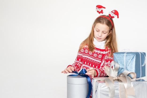 Mooi klein meisje dat de zitting van de kerstmishoofdband draagt ?? die op wit oppervlak wordt geïsoleerd