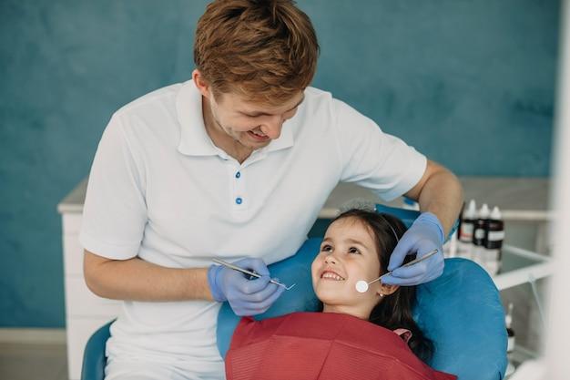 Mooi klein meisje dat haar tandarts bekijkt die glimlacht alvorens een tandenonderzoek te doen.