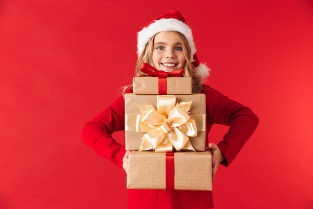 Mooi klein meisje dat kerstmishoed draagt die zich geïsoleerd bevindt, die stapel huidige dozen houdt