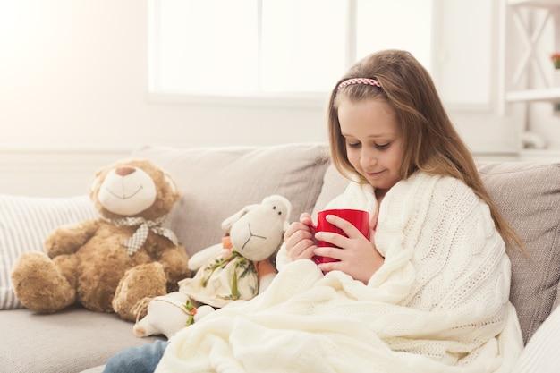 Mooi klein meisje dat thee drinkt, zittend op de bank gewikkeld in een witte gebreide deken. schattige peinzende jongen met tijdverdrijf thuis op de bank met haar speelgoed, kopieer ruimte