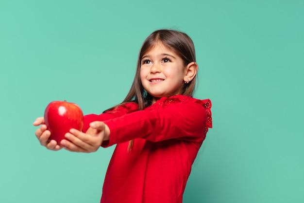 Mooi klein meisje dat uitdrukking denkt en een appel vasthoudt