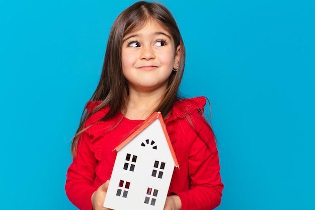 Mooi klein meisje dat uitdrukking denkt en een huismodel vasthoudt