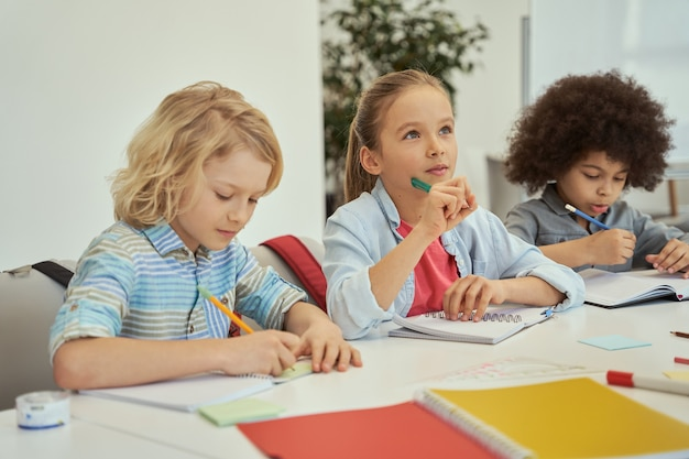 Mooi klein meisje dat wegkijkt terwijl ze luistert naar leraarskinderen die studeren en aantekeningen maken