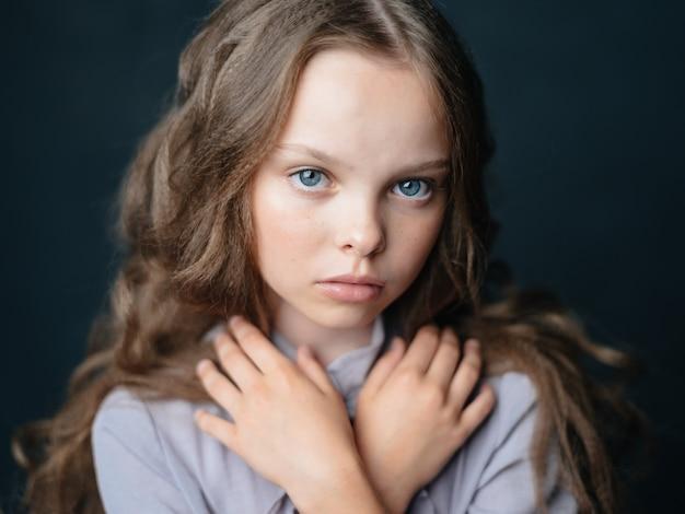 Mooi klein meisje droevig gezicht donkere achtergrond en grijs kledingsportret
