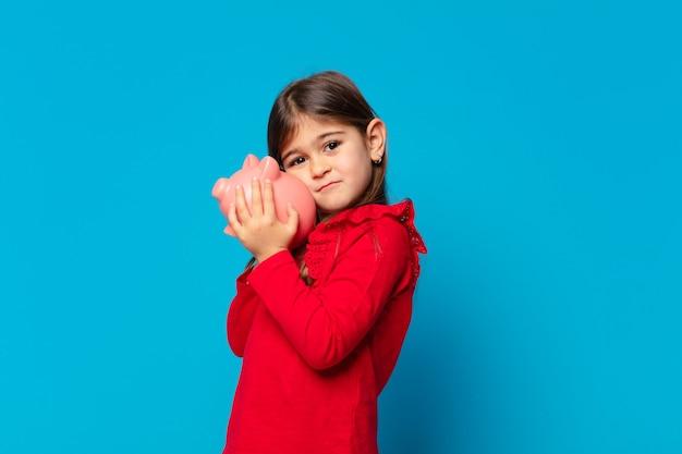 Mooi klein meisje droevige uitdrukking en met een spaarvarken