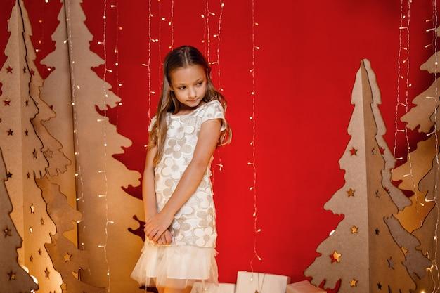 Mooi klein meisje droomt van kerstcadeaus. rode kerstversiering, ongebruikelijk. de avond voor kerst, kerstavond