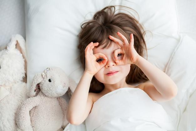 Mooi klein meisje dwaas liggend in een wit bed met konijn speelgoed liggen in de buurt. bovenaanzicht.