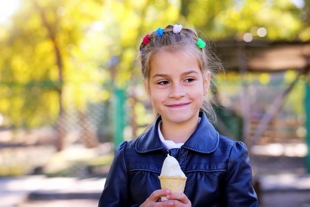 Mooi klein meisje eet ijs in de herfst