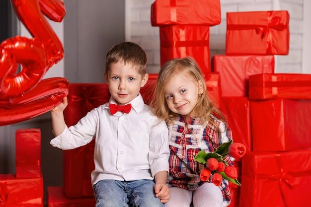 Mooi klein meisje en jongen vieren de dag van de valentijnskaart van sint
