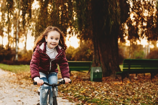 Mooi klein meisje fietsen in het park tegen zonsondergang tijdens het kijken naar camera glimlachen.