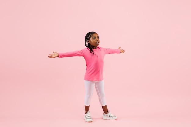 Mooi klein meisje geïsoleerd op koraal roze achtergrond.