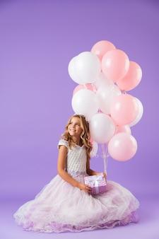 Mooi klein meisje gekleed in prinsessenjurk zitten geïsoleerd over violette muur, met een bos ballonnen en een geschenkdoos