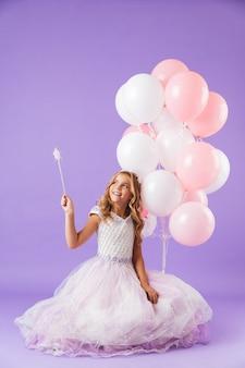 Mooi klein meisje gekleed in prinsessenjurk zitten geïsoleerd over violette muur, met een bos ballonnen en een magische toverstaf