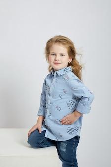 Mooi klein meisje glimlacht, kind in herfstkleren poseert op een witte achtergrond