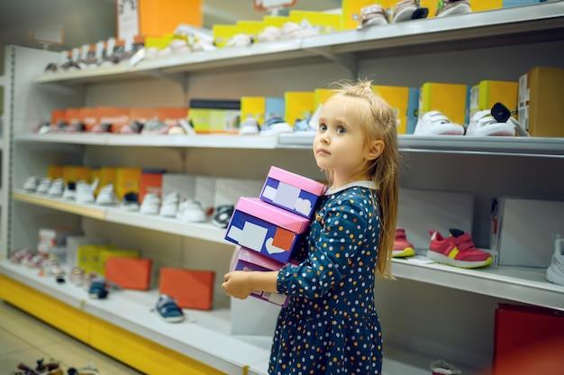 Mooi klein meisje houdt doos met schoenen in de kinderwinkel