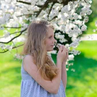 Mooi klein meisje in bloeiende appelboom tuin op een mooie lentedag