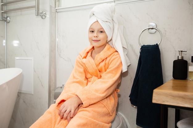 Mooi klein meisje in de badkamer in een badjas