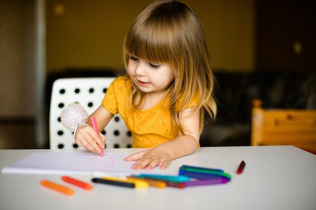 Mooi klein meisje in de gele jurk tekenen met wax pastel
