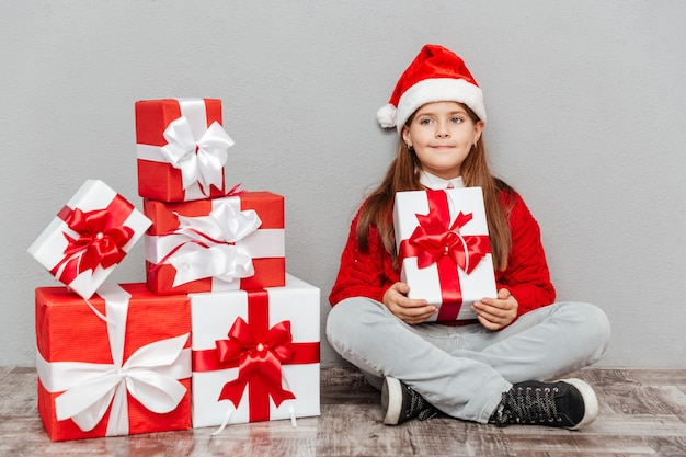 Mooi klein meisje in de hoed van de kerstman zit en houdt een geschenkdoos vast