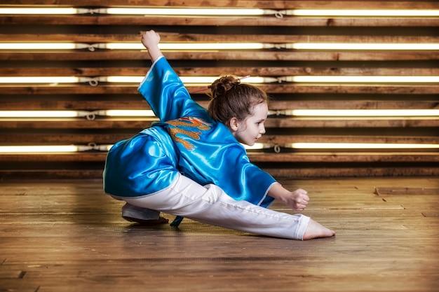 Mooi klein meisje in de kamer in sportkleding voor vechtsporten is wushu of kungfu