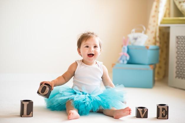 Mooi klein meisje in een blauwe gezwollen rok zit op de vloer in een gezellige woonkamer met liefde blokjes.