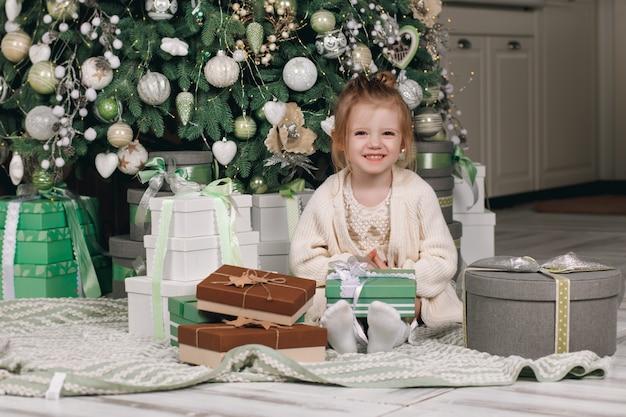 Mooi klein meisje in een jurk met een cadeau in haar hand zit in de buurt van de kerstboom