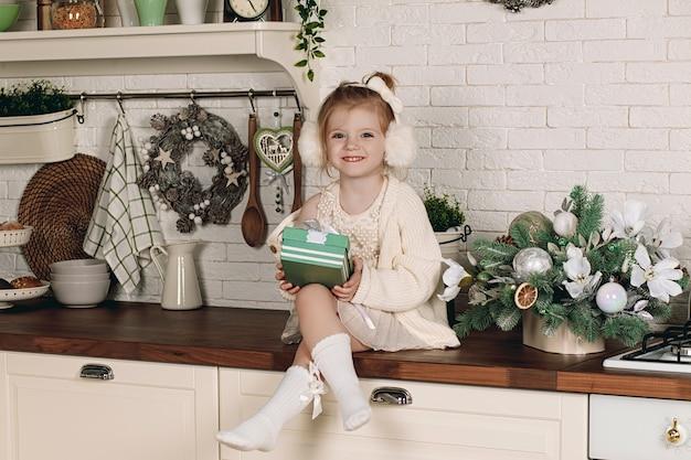 Mooi klein meisje in een jurk met een cadeau in haar hand zittend op de keukentafel