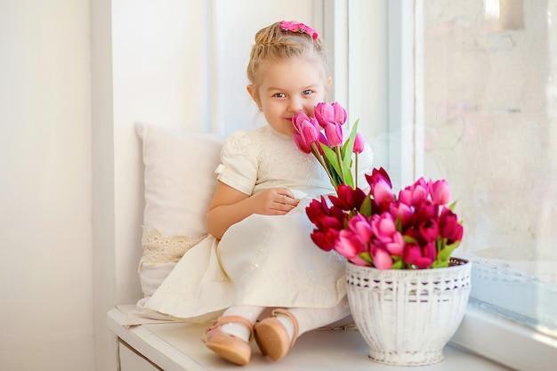 Mooi klein meisje in een witte jurk zittend op een vensterbank met een boeket roze tulpen