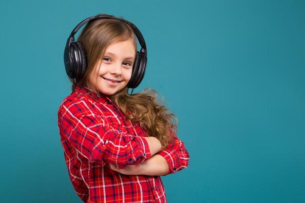 Mooi, klein meisje in geruit hemd en oortelefoons met bruin haar