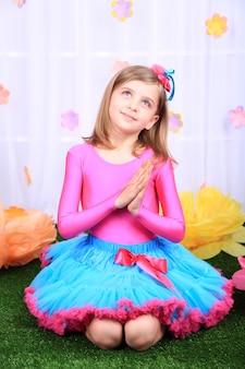 Mooi klein meisje in kleine rok op decoratieve achtergrond