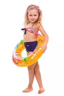 Mooi klein meisje in rood gestreepte bikini, blauwe bodems en roze krans staan met kleurrijke rubberen ring in de taille
