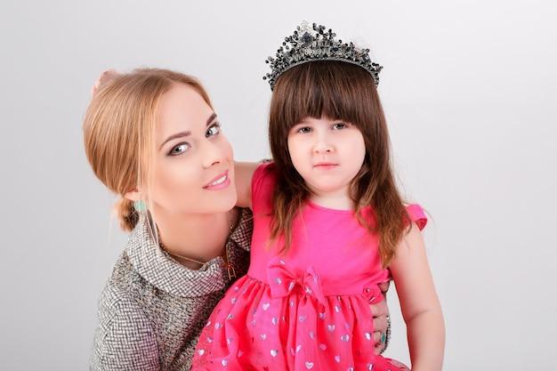 Mooi klein meisje in roze prinses jurk met een kroon erboven en mooie moeder knuffelen op een grijze achtergrond.