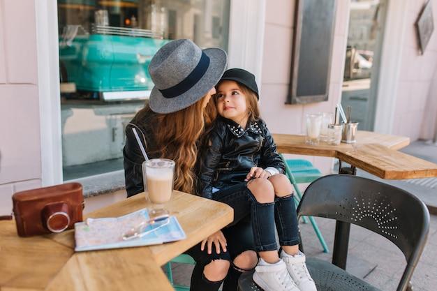 Mooi klein meisje in trendy jeans en zwarte jas, zittend op de knieën van moeder en haar met liefde te kijken.