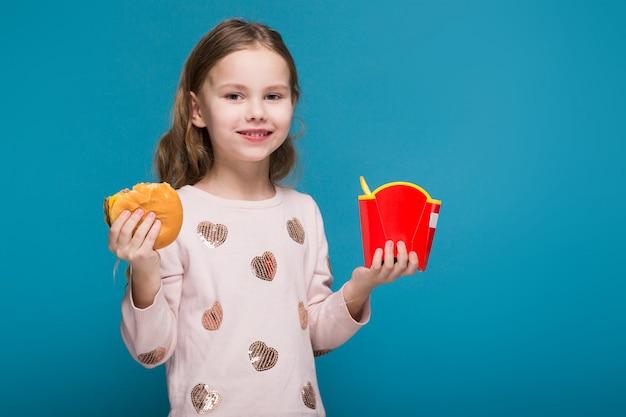 Mooi, klein meisje in trui met donkerbruin haar houdt een hamburger