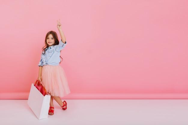Mooi klein meisje in tule rok met pakket met huidige wandelen geïsoleerd op roze achtergrond, glimlachend naar de camera. leuk vriendelijk kind echte positieve emoties uitdrukken. plaats voor tekst