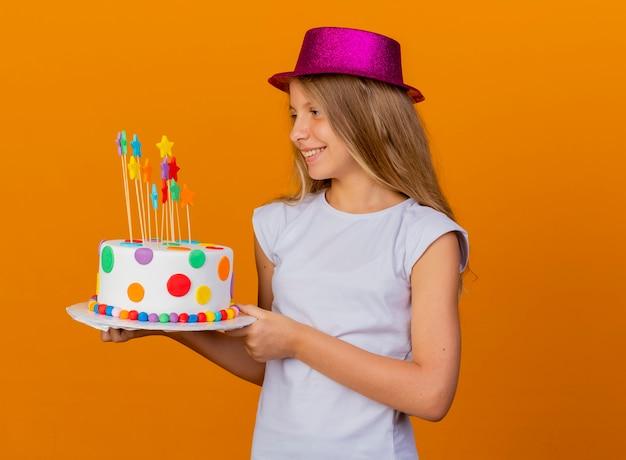 Mooi klein meisje in vakantie hoed bedrijf verjaardagstaart opzij kijken met glimlach op gezicht, verjaardagsfeestje concept permanent over oranje achtergrond